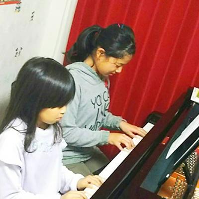ピアノを弾く2人の女性